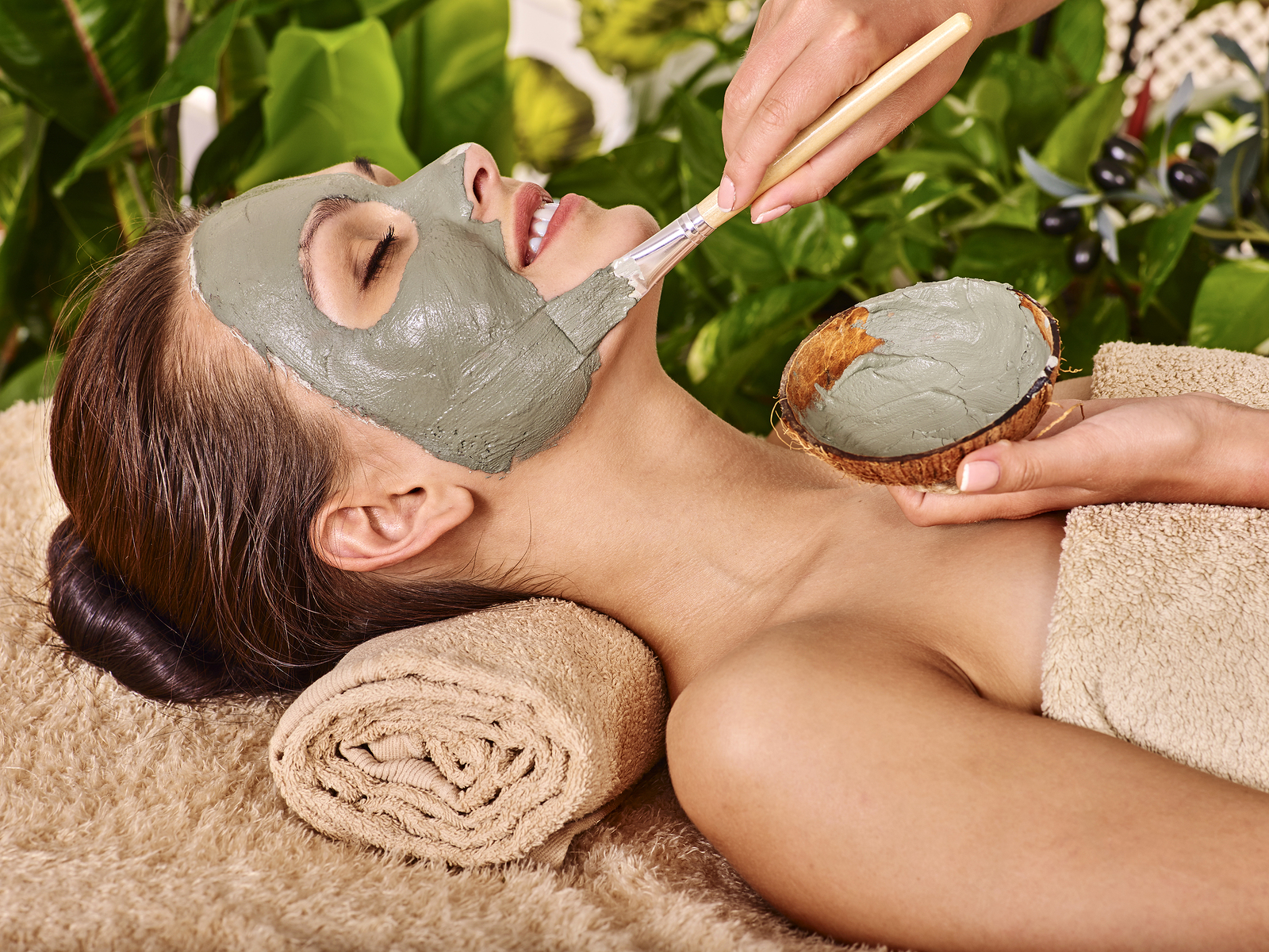Woman with clay facial mask in beauty spa. In background tropica